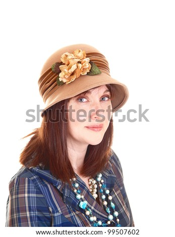 A portrait of a beautiful middle aged woman in a blue shirt and necklace with a beige hat with flowers on, and red hair for white background. - stock photo