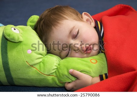A portrait of a beautiful sleeping baby, clasping a plush toy - stock photo