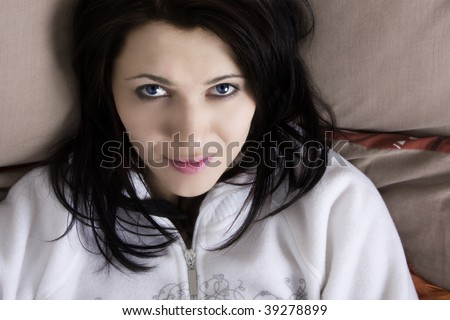 A portrait of a beautiful woman laying on a bed looking upwards. - stock photo