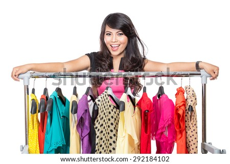 A portrait of a beautiful woman posing on the rack of clothes in a shop - stock photo