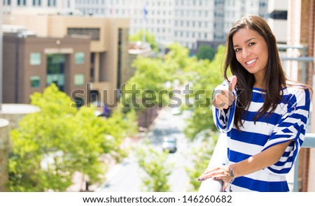 A portrait of a beautiful woman relaxing on a balcony of her apartment on a summer day, giving a thumbs up on a background of a city