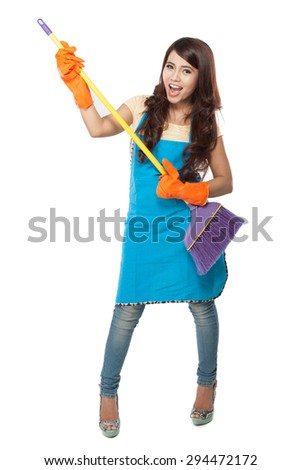 A portrait of a beautiful young asian woman holding a broom, use it like a guitar while smiling to the camera
