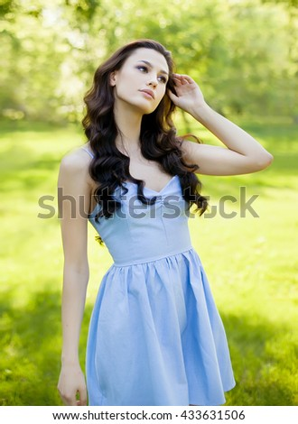A portrait of a beautiful young caucasian woman outdoor. Soft sunny colors. Sweet girl, clean skin, long dark hair. - stock photo