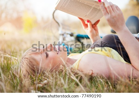 A portrait of a beautiful young Caucasian woman reading a book outdoor - stock photo