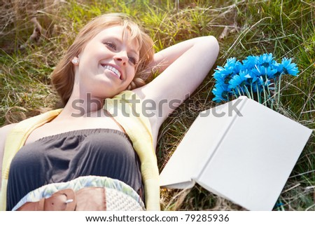 A portrait of a beautiful young Caucasian woman relaxing on the grass outdoor - stock photo