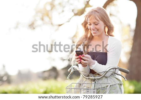 A portrait of a beautiful young Caucasian woman texting on her phone outdoor - stock photo