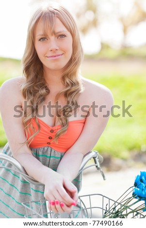 A portrait of a beautiful young Caucasian woman with her bike outdoor - stock photo