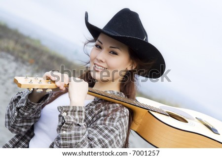 A portrait of a beautiful young woman carrying a guitar - stock photo