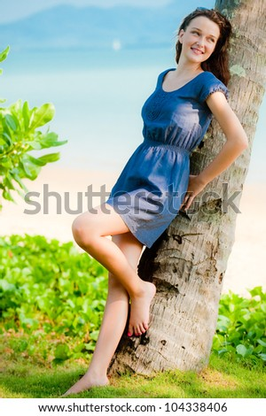A portrait of a beautiful young woman leaning on a palm tree - stock photo