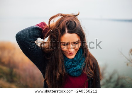 A portrait of a beautiful young woman outdoor. River background - stock photo