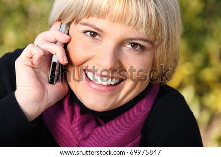 A portrait of a beautiful young woman talking on the phone over natural background - stock photo