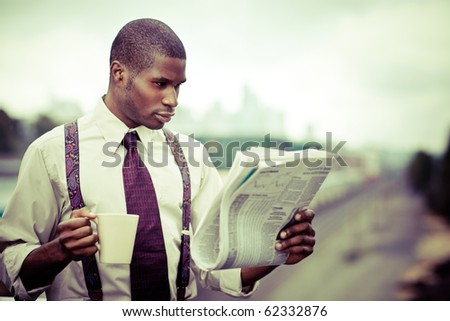 A portrait of a black businessman reading newspaper outdoor - stock photo