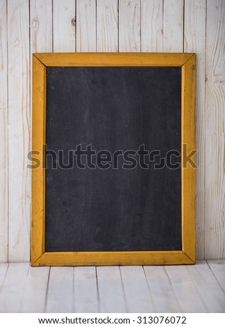 A portrait of a black chalkboard on wooden background, vertically placed - stock photo