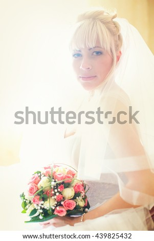 A portrait of a blonde bride with a rose bouquet sitting in a halo