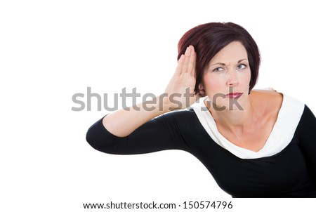A portrait of a carefully listening, nosy business woman  with hand to ear. Young attractive businesswoman in black dress isolated on a white background.Violation of privacy concept. - stock photo