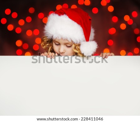 A portrait of a curious sweet little curly girl in Santa hat looking out from behind empty blank, isolated against Christmas glitter close up. Holidays concept. Invitation. Funny kids. - stock photo