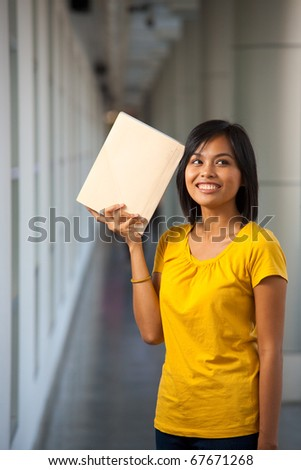 A portrait of a cute college student in yellow t-shirt thinking with a book against her head on a modern university campus.  Young female Asian Thai model late teens, early 20s of Chinese descent