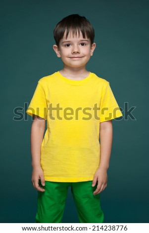 A portrait of a cute little boy in the yellow shirt against the green background