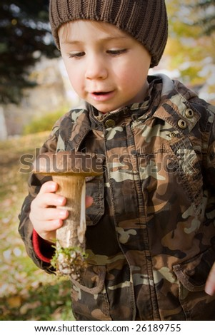 A portrait of a cute little boy wearing warm clothes, holding a mushroom freshly picked up.