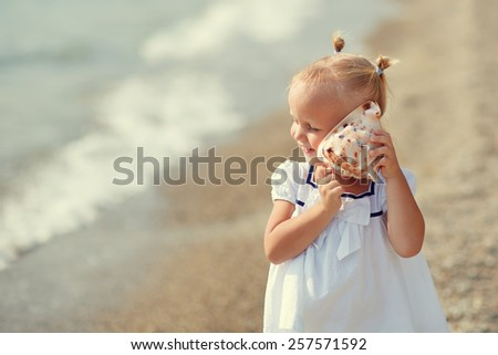 A portrait of a cute little girl in white clothes playing with a shell on the beach on a warm sunny summer day. Holidays at sea. Funny kids - stock photo
