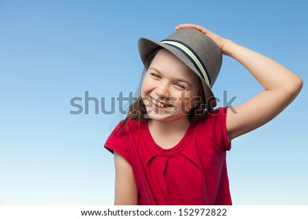 A portrait of a cute little girl, she is standing outside, wearing a hat and a red shirt against a blue sky,she is laughing - stock photo