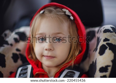 A portrait of a cute little girl sitting in safety car seat close up - stock photo