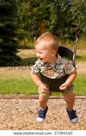 A portrait of a cute one year old baby boy on a swing. - stock photo