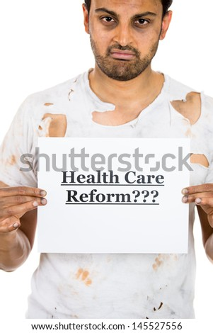 """A portrait of a desperate unhappy homeless man holding a sign """"health care reform???"""" hoping for universal health care coverage, isolated on a white background. politics, government , legislation  - stock photo"""