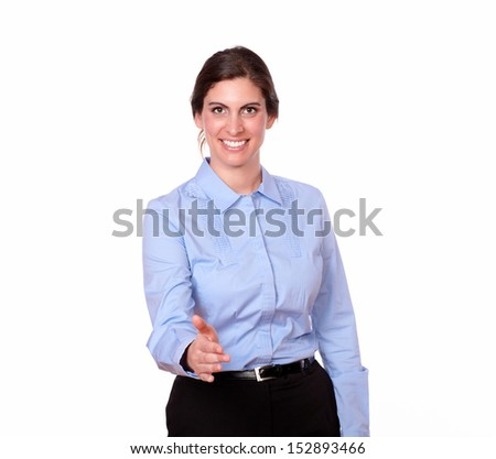 A portrait of a fashionable female standing with greeting gesture while smiling and looking at you on isolated background