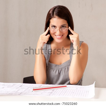 A portrait of a female architect looking at blueprints - stock photo