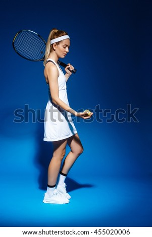 A portrait of a female tennis player with racket and ball in studio - stock photo