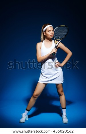 A portrait of a female tennis player with racket in studio - stock photo