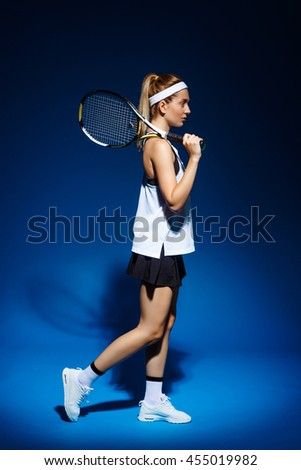 A portrait of a female tennis player with racket on the shoulder posing in studio - stock photo