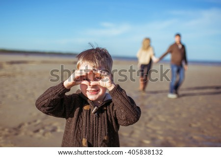 A portrait of a five-year-old boy holding hands like a mask at the beach on a sunny morning and his  parents coming hand-in-hand. - stock photo
