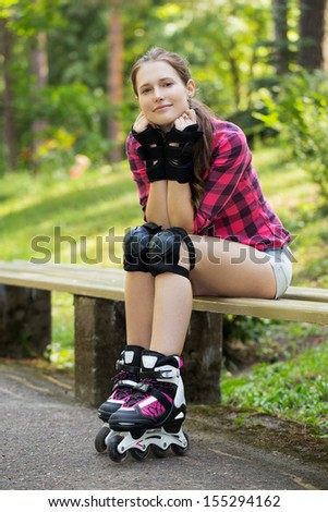 A portrait of a girl with rollerblades, who is sitting on a branch in a park - stock photo