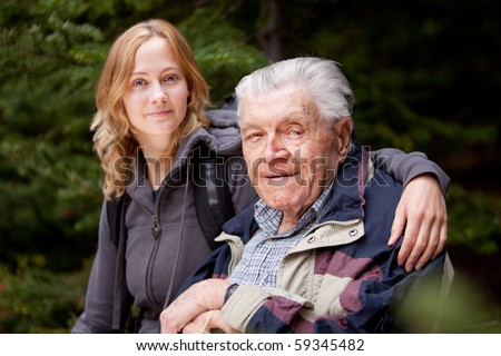 A portrait of a granddaughter with her grandfather in the forest - stock photo