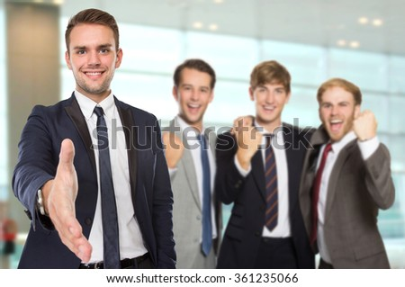 A portrait of a group of Young caucasian businessmen with success gesture. offering handshake - stock photo