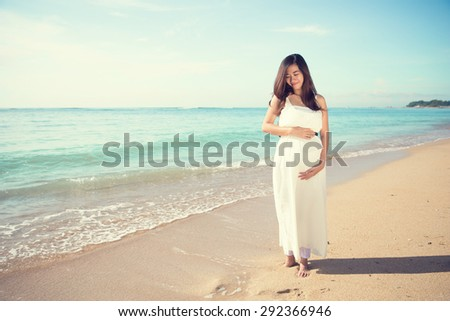 A portrait of a happy asian pregnant woman smile while touching her tummy on the beach - stock photo