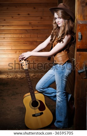 A portrait of a happy beautiful caucasian cowgirl with a guitar - stock photo