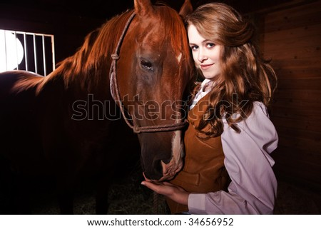 A portrait of a happy beautiful caucasian cowgirl with a horse - stock photo