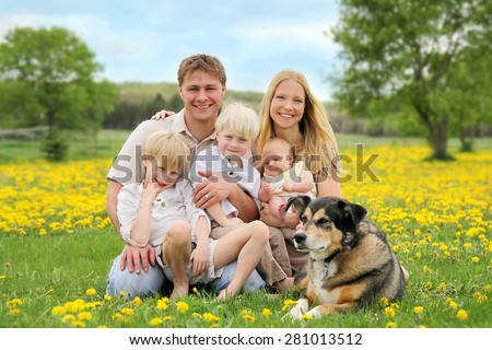 A portrait of a happy family of five caucasian people, including big brother, toddler boy, and baby sister are relaxing in a yellow Dandelion flower meadow with their pet dog. - stock photo