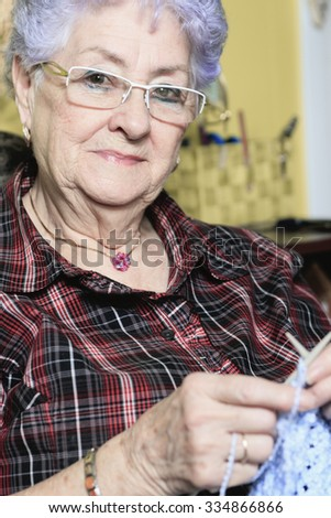 A Portrait of a happy senior woman at home knit on the sofa.