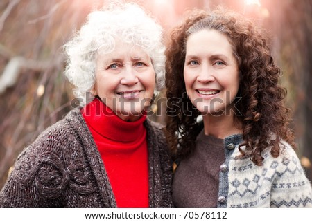 A portrait of a happy senior woman with her adult daughter