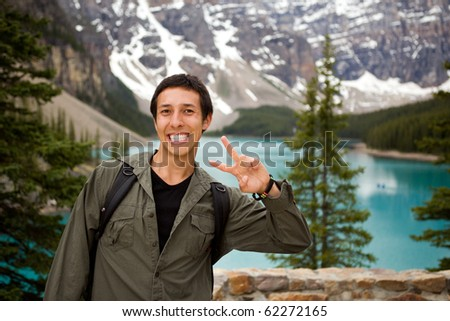 A portrait of a happy tourist in front of a scenic landscape