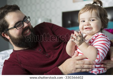 A Portrait of a happy young father with a baby in the bed at home - stock photo