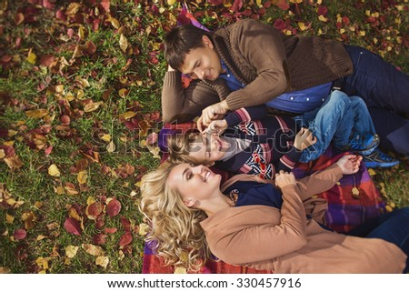 A portrait of a happy young parents with their child lay on a plaid in a park in autumn. Top view - stock photo