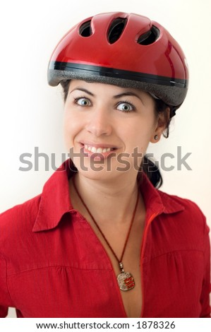 A portrait of a happy young woman wearing a red bicycle helmet and a red shirt