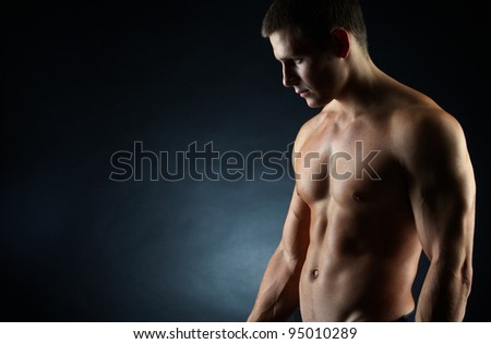 A portrait of a hot guy man without a shirt against dark background with copyspace - stock photo