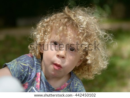 a portrait of a little boy with curly hair