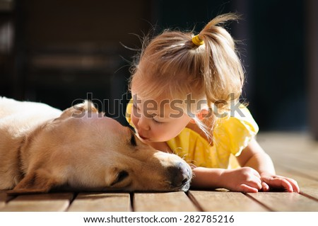 A portrait of a little cute toddler girl kissing her dog, a yellow labrador relaxing on the wooden deck in the sun - stock photo